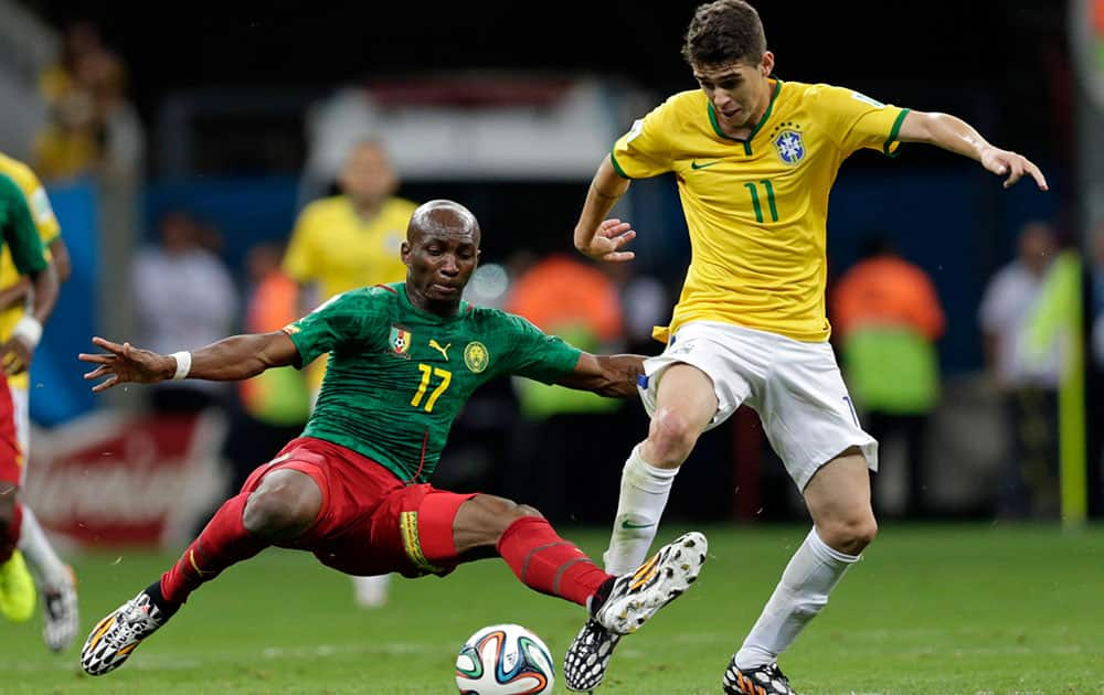 Cameroon's Stephane Mbia, left, and Brazil's Oscar challenge for the ball during the group A World Cup soccer match between Cameroon and Brazil at the Estadio Nacional in Brasilia, Brazil.