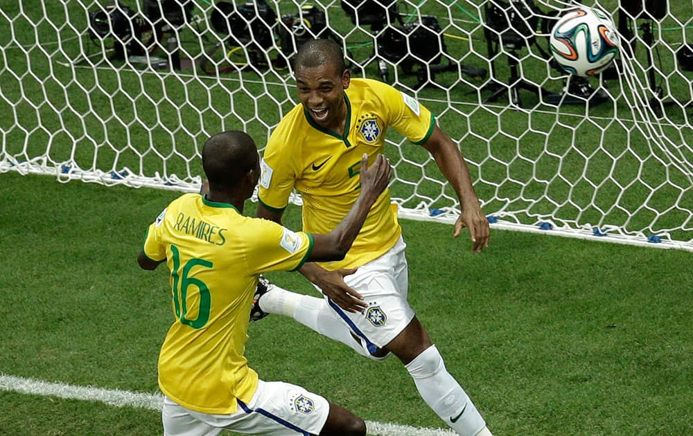 Brazil's Fernandinho, right, celebrates scoring his side's 5th goal during the group A World Cup soccer match between Cameroon and Brazil at the Estadio Nacional in Brasilia, Brazil.