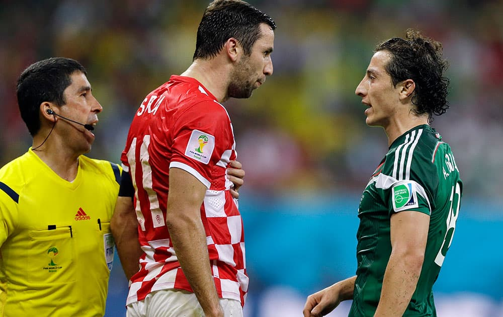 A linesman tries to prevent Croatia's Darijo Srna, center, from clashing with Mexico's Andres Guardado during the group A World Cup soccer match between Croatia and Mexico at the Arena Pernambuco in Recife, Brazil.