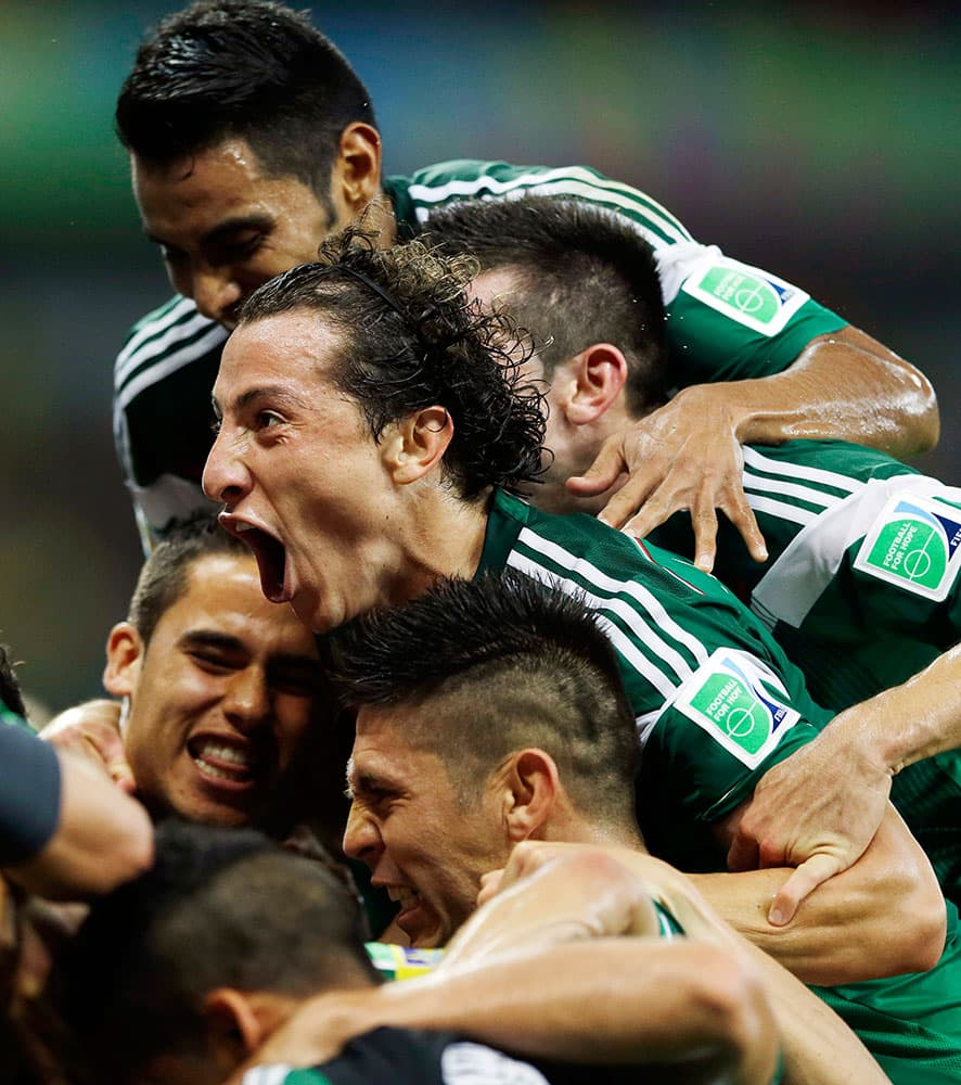 Mexico's Andres Guardado celebrates with teammates after Mexico's Rafael Marquez scored his team's first goal during the group A World Cup soccer match between Croatia and Mexico at the Arena Pernambuco in Recife, Brazil.