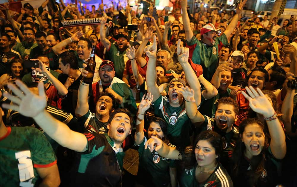 Mexico soccer fans celebrate a goal scored by their team on a street of Copacabana, in Rio de Janeiro, Brazil.