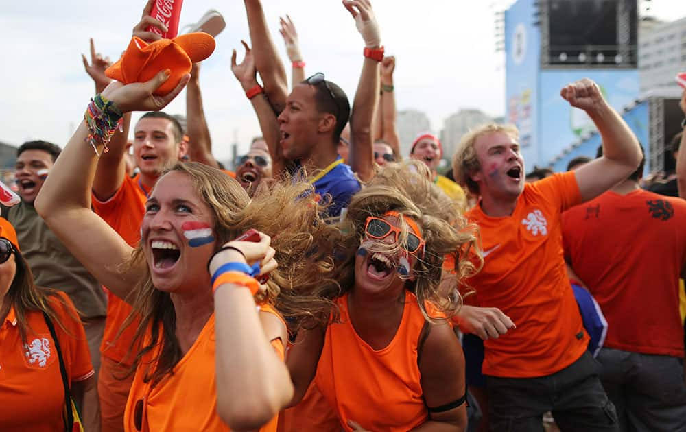 Soccer fans, decked out in orange, the Netherlands' national color, celebrate the second goal scored by Memphis Depay, while watching a live broadcast of the group B World Cup match between Chile and Netherlands, inside the FIFA Fan Fest area on Copacabana beach, in Rio de Janeiro, Brazil.