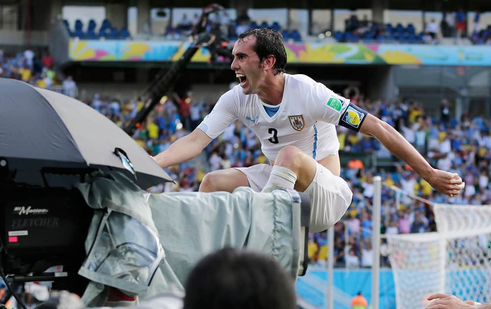 Uruguay's Diego Godin leaps over a barricade next to a television camera as he celebrates after scoring his side's first goal during the group D World Cup soccer match between Italy and Uruguay at the Arena das Dunas in Natal, Brazil.