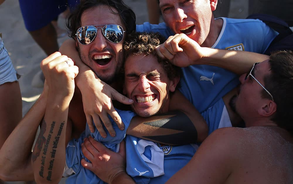 Uruguay soccer fans celebrate their team's 1-0 victory over Italy at a World Cup game after watching a live telecast inside the FIFA Fan Fest area on Copacabana beach in Rio de Janeiro, Brazil.