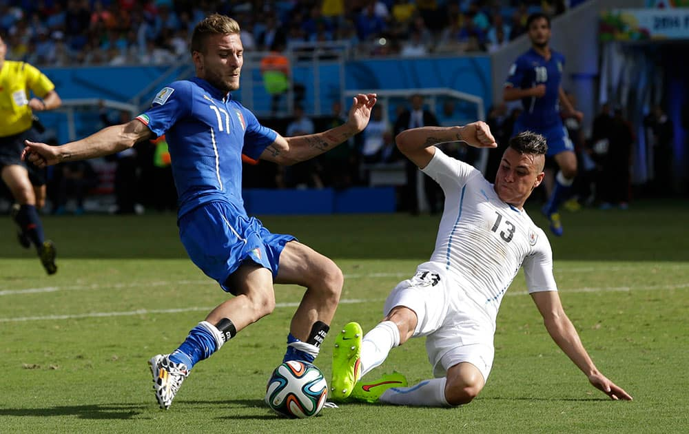 Italy's Ciro Immobile, left, is challenged by Uruguay's Jose Maria Gimenez during the group D World Cup soccer match between Italy and Uruguay at the Arena das Dunas in Natal, Brazil.