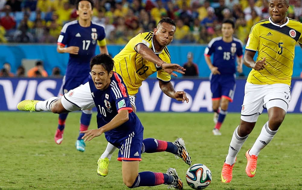 Japan's Shinji Kagawa, front, brings down Colombia's James Rodriguez during the group C World Cup soccer match between Japan and Colombia at the Arena Pantanal in Cuiaba, Brazil.