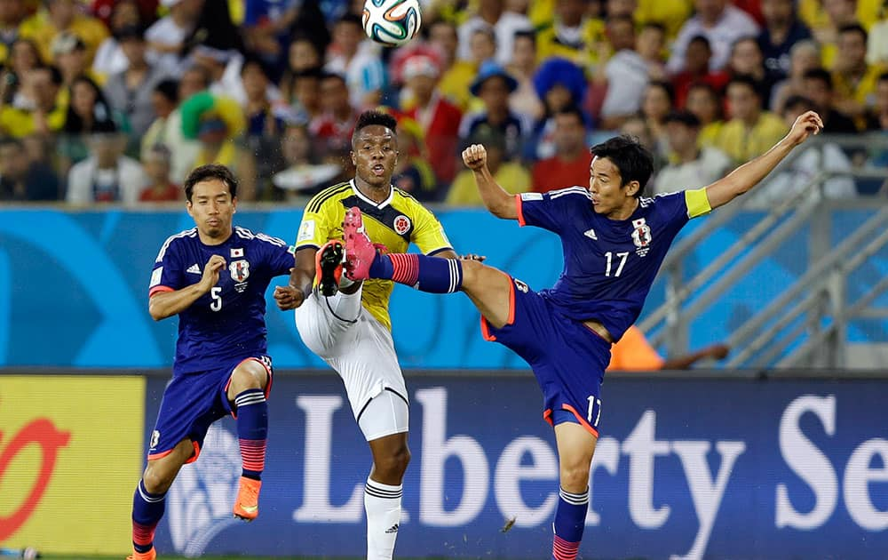 Japan's Yuto Nagatomo (5) and Japan's Makoto Hasebe (17) challenge Colombia's Carlos Carbonero during the group C World Cup soccer match between Japan and Colombia at the Arena Pantanal in Cuiaba, Brazil.