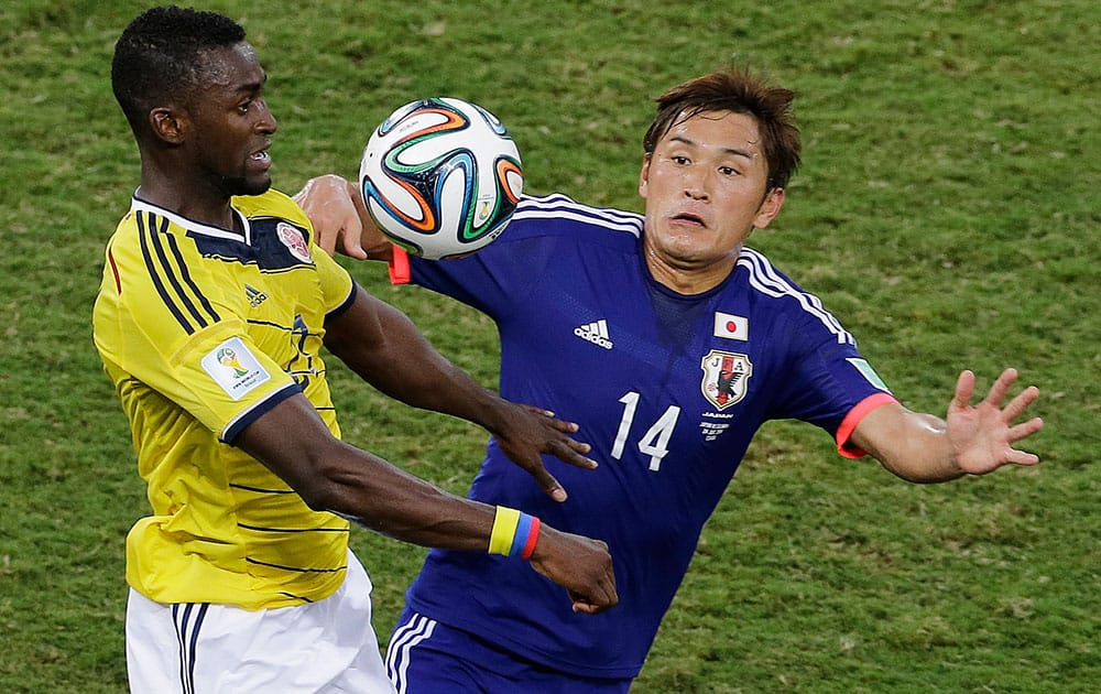 Japan midfielder Toshihiro Aoyama, right, heads the ball away defender from Colombia during the second half of a group C World Cup soccer match at the Arena Pantanal in Cuiaba, Brazil.
