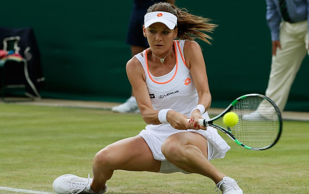Agnieszka Radwanska of Poland plays a return to Andreea Mitu of Romania during their first round match at the All England Lawn Tennis Championships in Wimbledon.