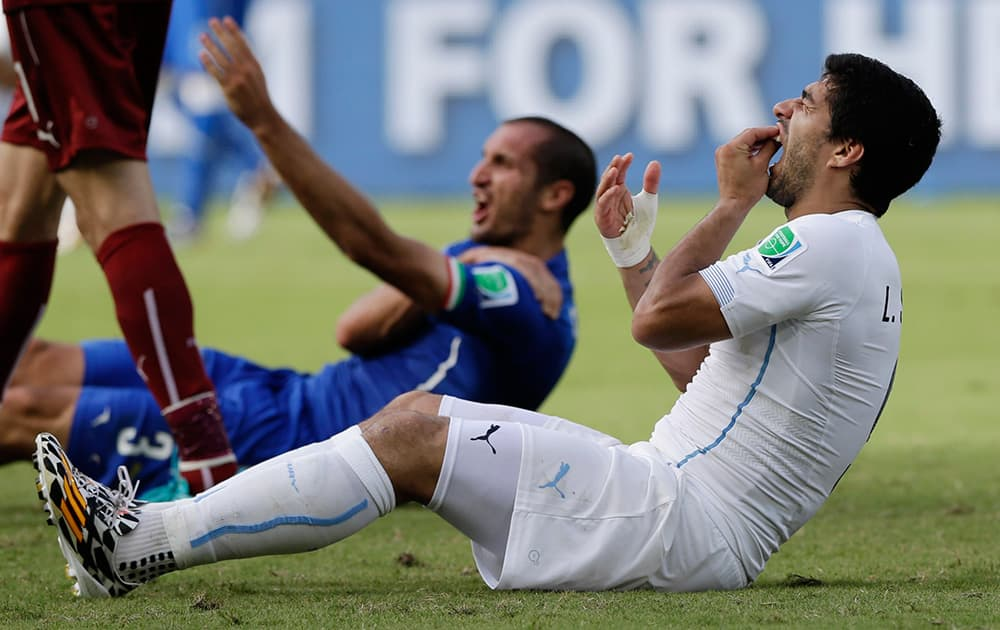 Uruguay's Luis Suarez holds his teeth after running into Italy's Giorgio Chiellini's shoulder during the group D World Cup soccer match between Italy and Uruguay at the Arena das Dunas in Natal, Brazil.