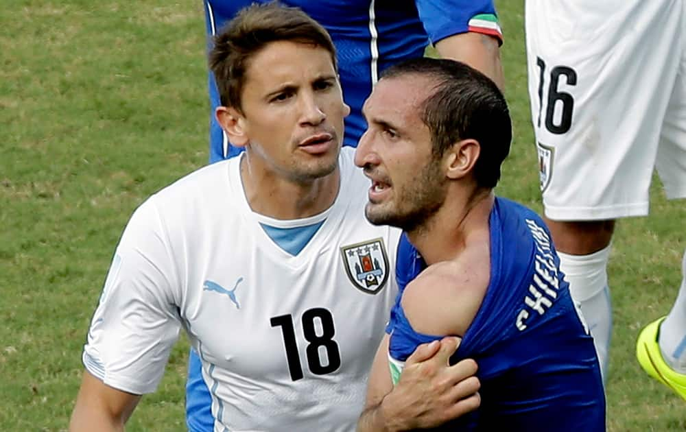 Italy's Giorgio Chiellini shows his shoulder after colliding with Uruguay's Luis Suarez's mouth as Uruguay's Gaston Ramirez (18) watches during the group D World Cup soccer match between Italy and Uruguay at the Arena das Dunas in Natal, Brazil.