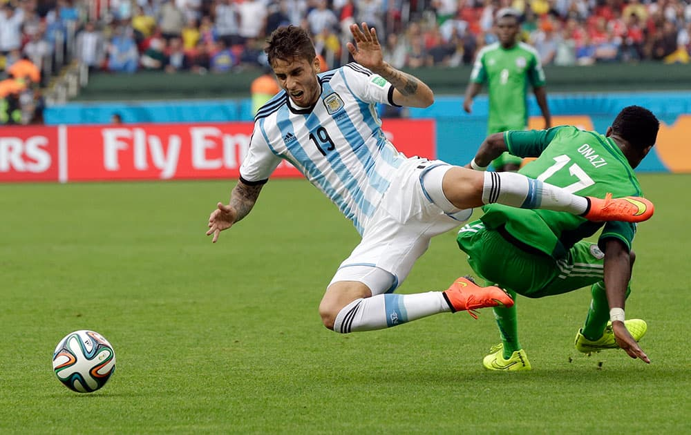 Argentina's Ricardo Alvarez falls over Nigeria's Ogenyi Onazi, right, during the group F World Cup soccer match between Nigeria and Argentina at the Estadio Beira-Rio in Porto Alegre, Brazil.