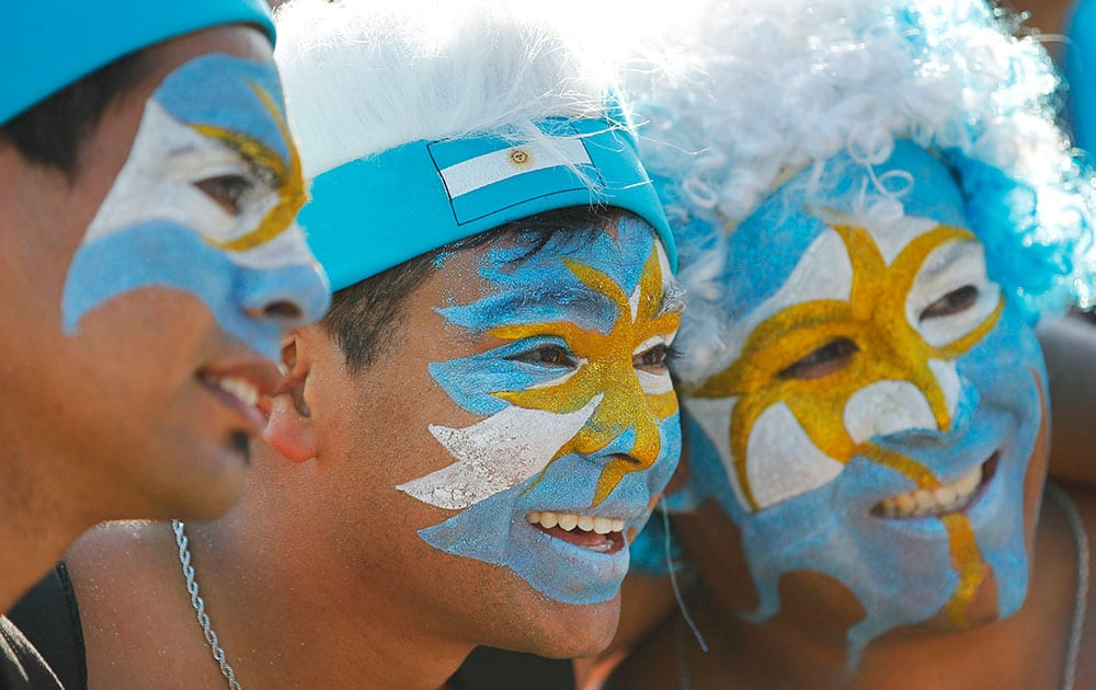 Argentina soccer fans, their faces painted to represent their country's national flag, pose for a photo during a live telecast of the World Cup group F match between Nigeria and Argentina, inside the FIFA Fan Fest area on Copacabana beach, in Rio de Janeiro, Brazil.