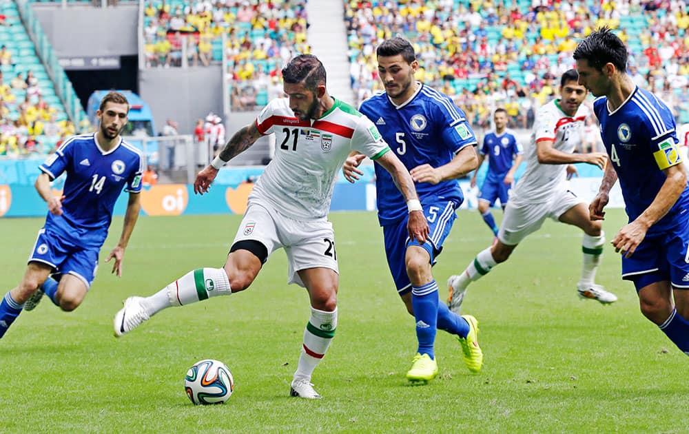 Iran's Ashkan Dejagah shoots a pass to Iran's Pejman Montazeri, rear, through Bosnia's Sead Kolasinac (5) and Emir Spahic (4), during the group F World Cup soccer match between Bosnia and Iran at the Arena Fonte Nova in Salvador, Brazil.