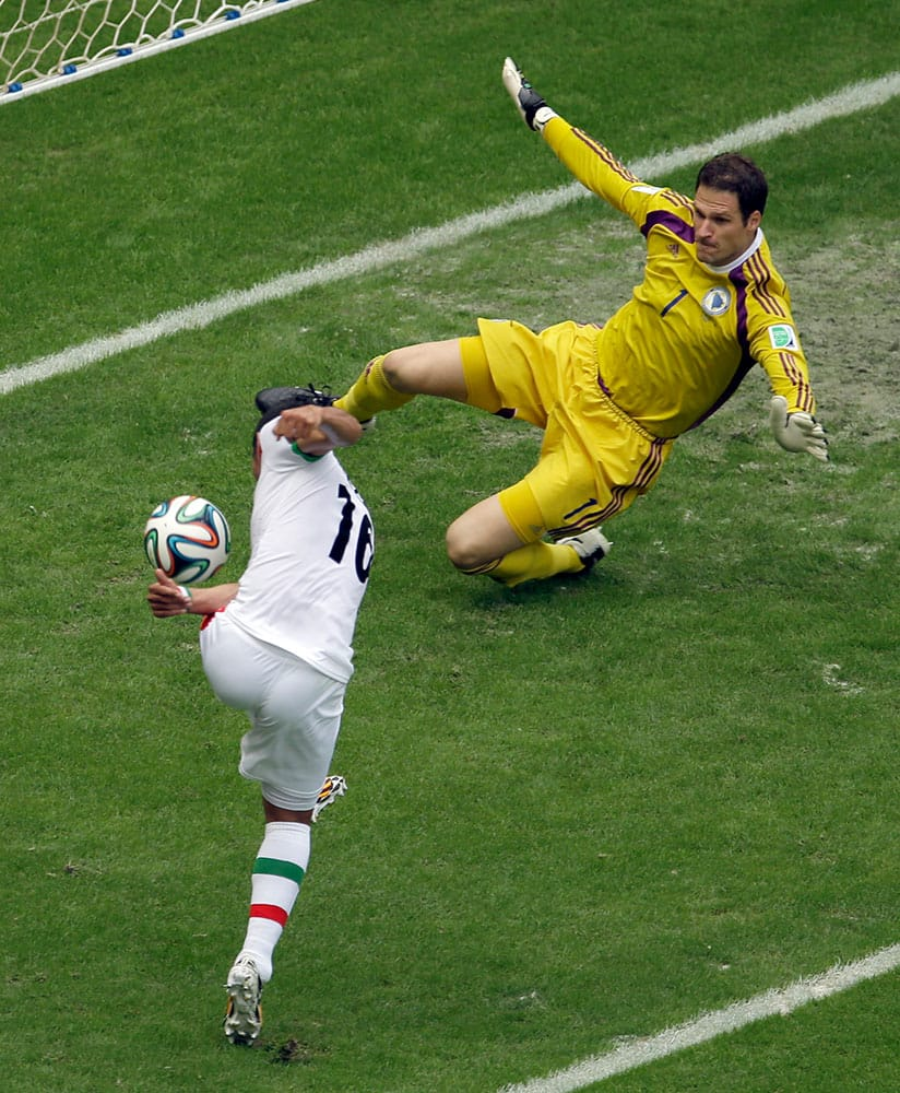 Bosnia goalie Asmir Begovic, top, blocks a shot by Iran forward Reza Ghoochannejhad during the first half of a group F World Cup soccer match at the Arena Fonte Nova in Salvador, Brazil.