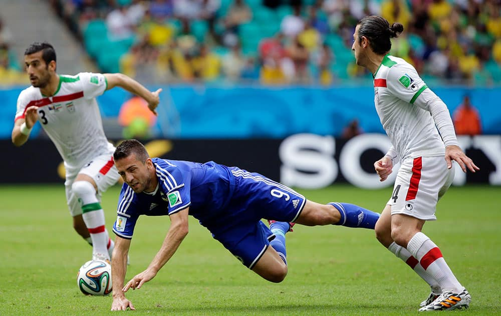 Bosnia's Vedad Ibisevic, center, is tripped by Iran's Andranik Teymourian, right, during the group F World Cup soccer match between Bosnia and Iran at the Arena Fonte Nova in Salvador, Brazil.