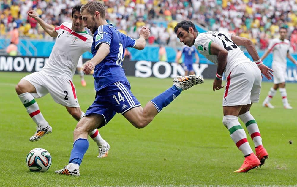 Bosnia's Tino-Sven Susic shoots a cross past Iran's Khosro Heydari, left, during the group F World Cup soccer match between Bosnia and Iran at the Arena Fonte Nova in Salvador, Brazil.