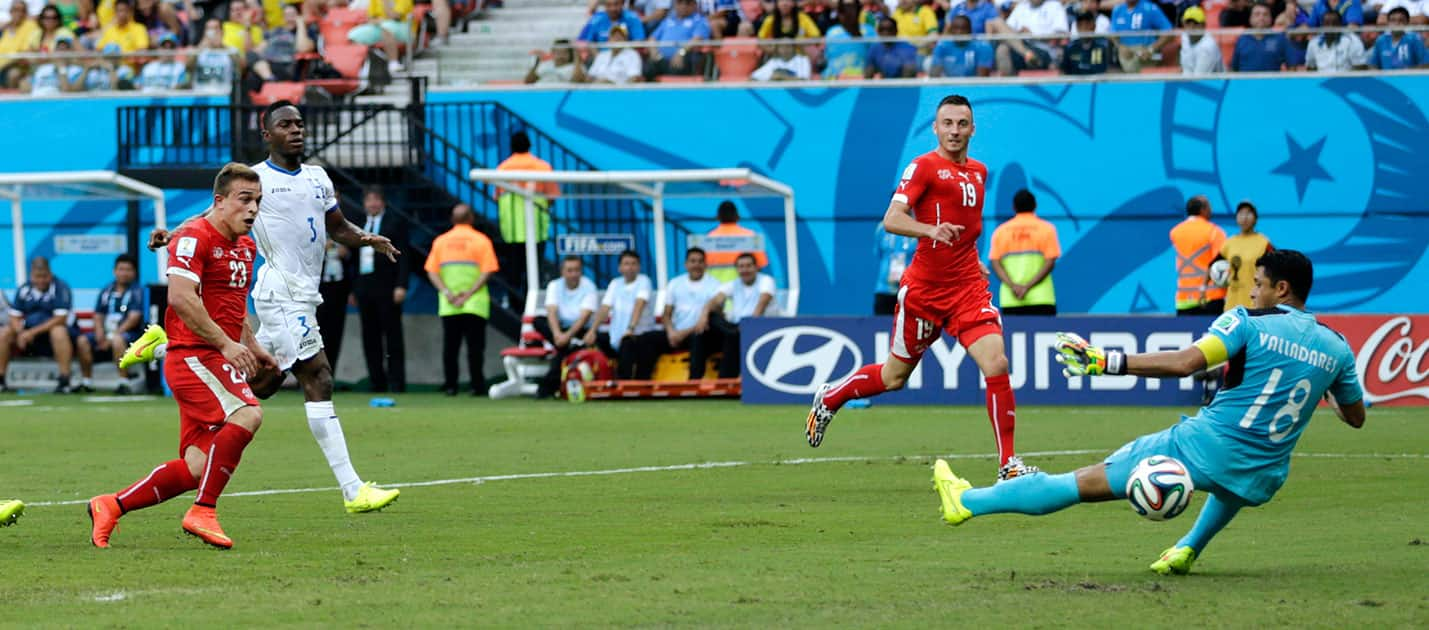 Switzerland's Xherdan Shaqiri, left, scores his team's second goal past Honduras' goalkeeper Noel Valladares (18) during the group E World Cup soccer match between Honduras and Switzerland at the Arena da Amazonia in Manaus, Brazil.