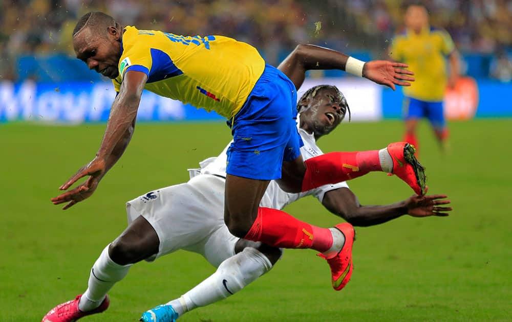 Ecuador's Walter Ayovi collides with France's Bacary Sagna during the group E World Cup soccer match between Ecuador and France at the Maracana Stadium in Rio de Janeiro, Brazil.
