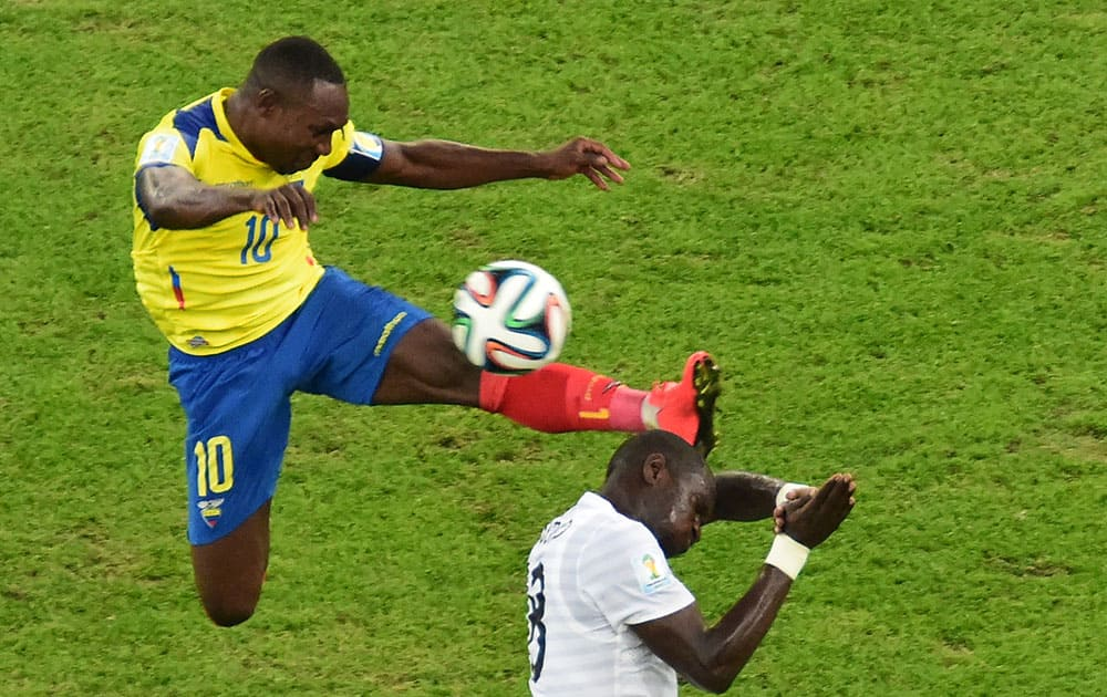 Ecuador's Walter Ayovi, left, and France's Moussa Sissoko challenge for the ball during the group E World Cup soccer match between Ecuador and France at the Maracana Stadium in Rio de Janeiro, Brazil.