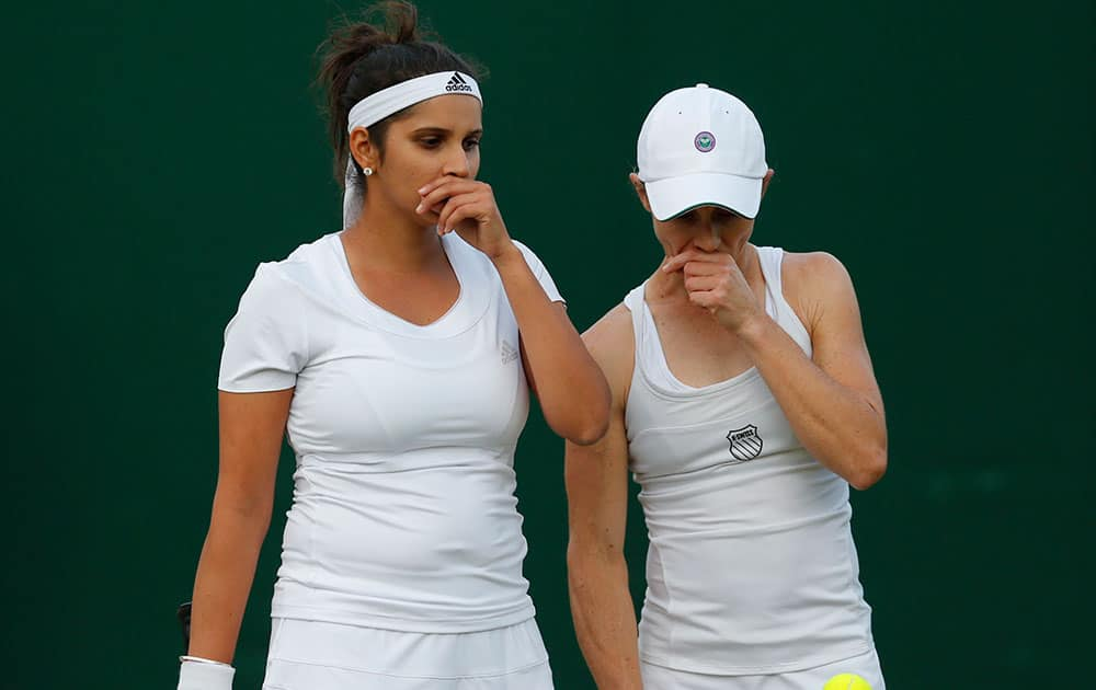 Sania Mizra  and playing partner Carla Black of Zimbabwe talk tactics as they play against Martina Hingis of Switzerland, and Vera Zonareva of Russia during the women's doubles match at the All England Lawn Tennis Championships in Wimbledon.