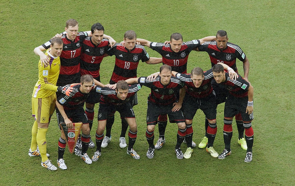 The team from Germany pose for their team photo before the group G World Cup soccer match between the USA and Germany at the Arena Pernambuco in Recife, Brazil