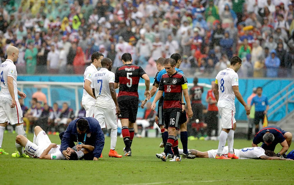 United States' Alejandro Bedoya, left, and United States' Jermaine Jones lie on the pitch after colliding during the group G World Cup soccer match between the USA and Germany at the Arena Pernambuco in Recife, Brazil.