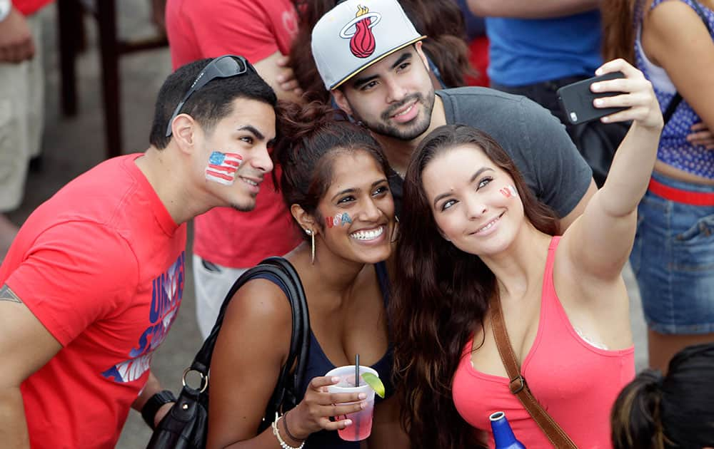 Soccer fans taking selfies while gathered at Lucky's Pub to view the United States World Cup soccer game against Germany, in Houston.
