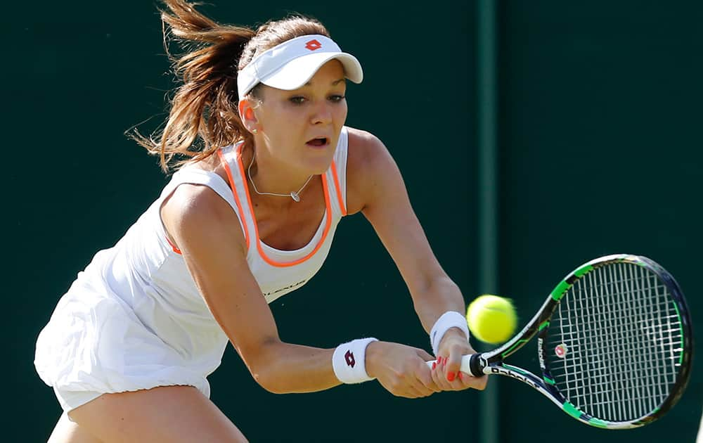Agnieszka Radwanska of Poland plays a return to Michelle Larcher De Brito of Portugal during their women's singles match at the All England Lawn Tennis Championships in Wimbledon, London.
