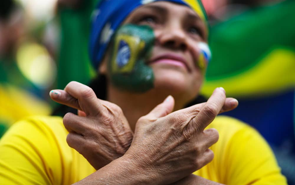 A Brazil soccer fan crosses her fingers as she watches a live telecast of the World Cup round of 16 match between Brazil and Chile inside the FIFA Fan Fest area in Sao Paulo, Brazil.