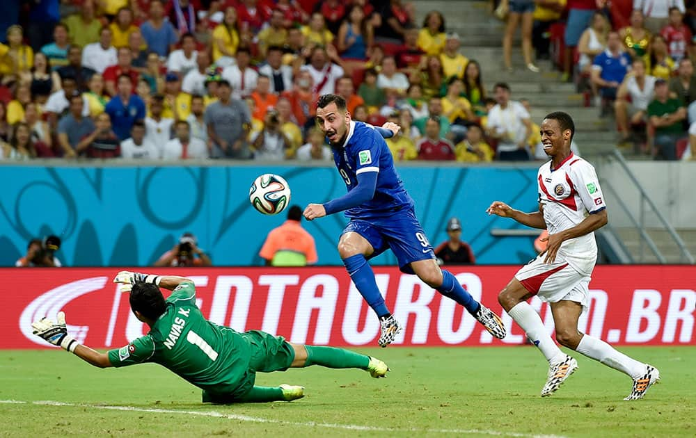 Costa Rica's goalkeeper Keylor Navas, left, makes a save on a shot by Greece's Kostas Mitroglou during extra time in the World Cup round of 16 soccer match between Costa Rica and Greece at the Arena Pernambuco in Recife, Brazil.