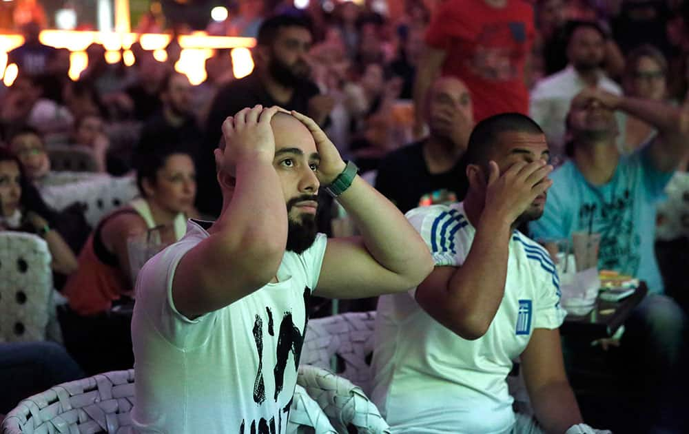 Greece's soccer fans react as they watch a World Cup match between Greece and Costa Rica via a live broadcast on a giant screen, at a mall in Athens, Greece.