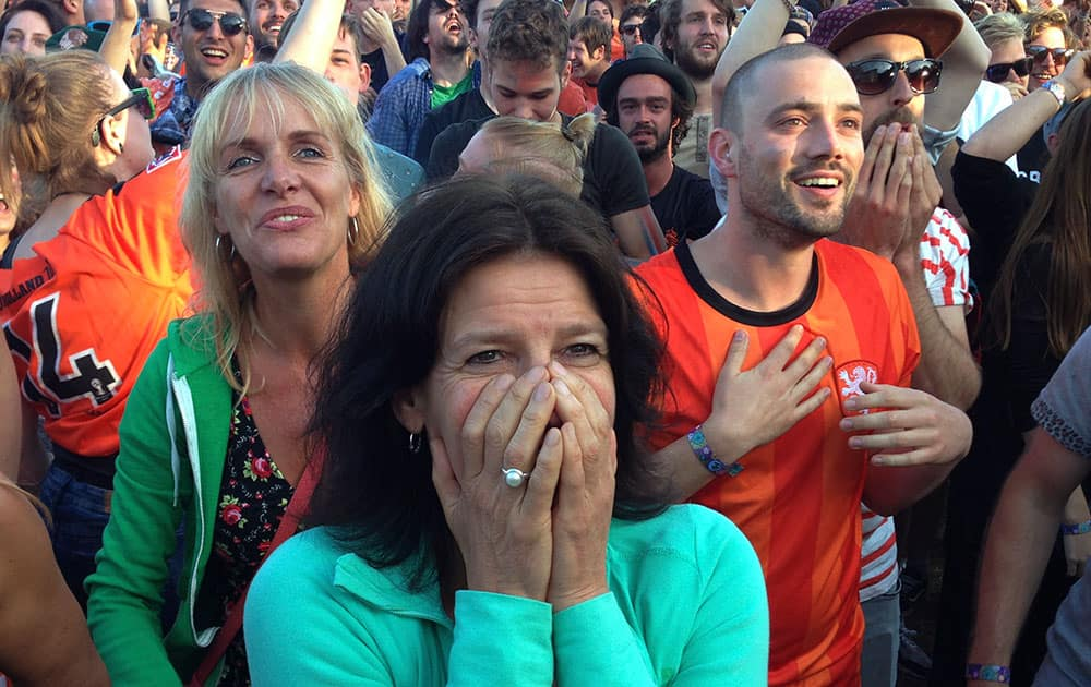 Festival goers celebrate as they watch the 2-1 win of the Dutch team in the World Cup round of 16 soccer match between the Netherlands and Mexico on the last day of the 'Down the Rabbit Hole' music festival in Beuningen, near Nijmegen.
