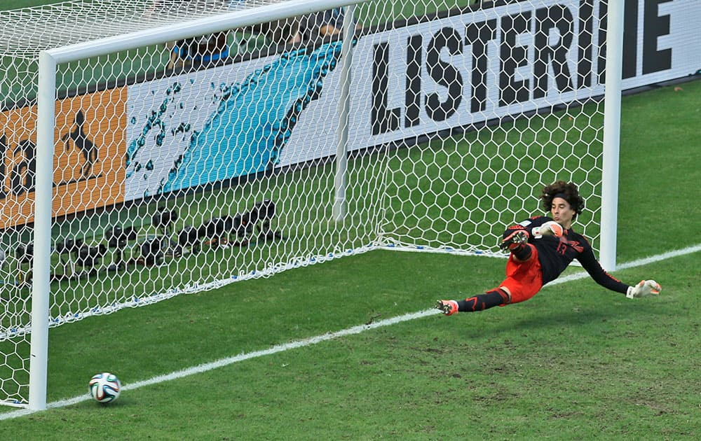 Mexico's goalkeeper Guillermo Ochoa fails to save a shot by Netherlands' Klaas-Jan Huntelaar from the penalty spot during the World Cup round of 16 soccer match between the Netherlands and Mexico at the Arena Castelao in Fortaleza, Brazil.