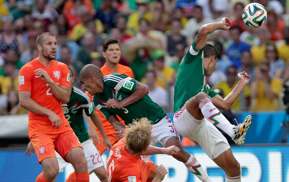 Netherlands' Dirk Kuyt, down, fights for the ball with Mexico's defenders during the World Cup round of 16 soccer match between the Netherlands and Mexico at the Arena Castelao in Fortaleza, Brazil.