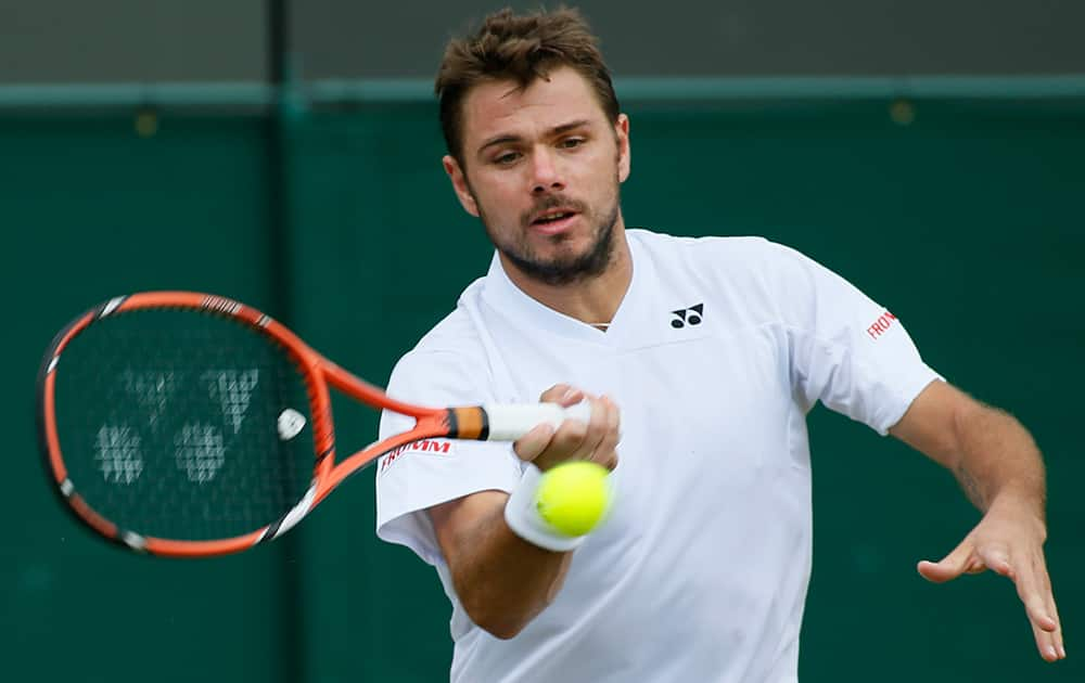 Stan Wawrinka of Switzerland plays a return to Denis Istomin of Uzbekistan during their match at the All England Lawn Tennis Championships in Wimbledon, London.