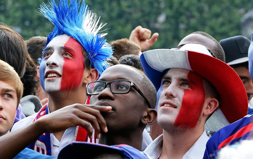 French soccer fans react as they watch the World Cup soccer match between France and Nigeria being shown live on a giant screen, in front of Paris City Hall.