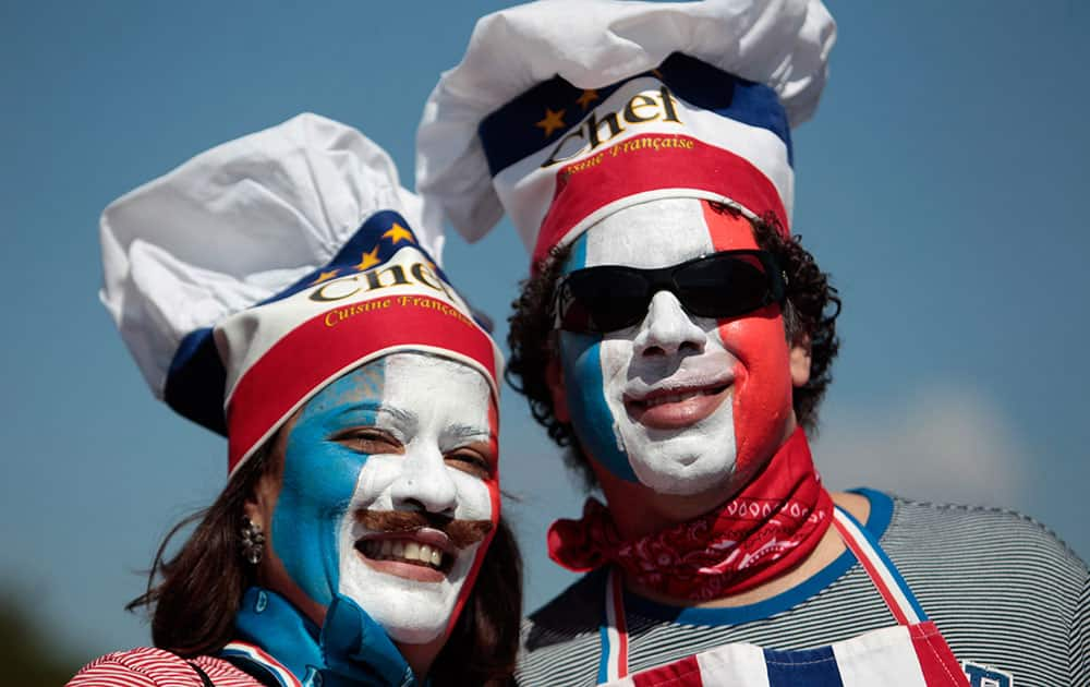 France soccer fans, with their faces painted with their team's colors arrive at the National Stadium to watch World Cup round of 16 match against Nigeria, in Brasilia, Brazil.