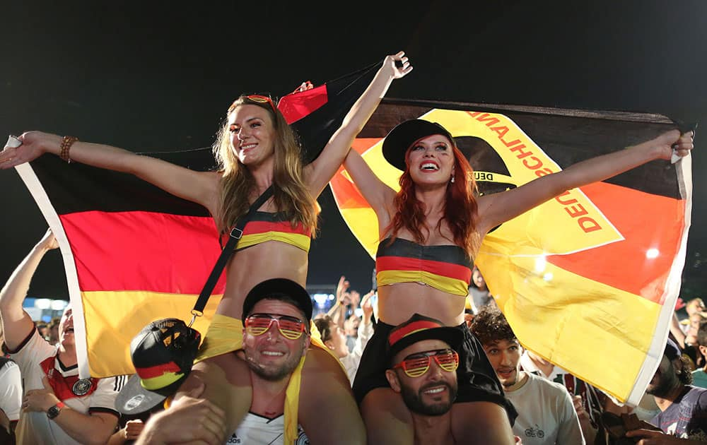 Germany soccer fans celebrate their team's victory over Algeria after watching the World Cup round of 16 match on a live telecast inside the FIFA Fan Fest area on Copacabana beach in Rio de Janeiro, Brazil.