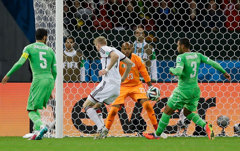 Germany's Andre Schuerrle scores his side's first goal against Algeria's goalkeeper Rais M'Bolhi during the World Cup round of 16 soccer match between Germany and Algeria at the Estadio Beira-Rio in Porto Alegre, Brazil.