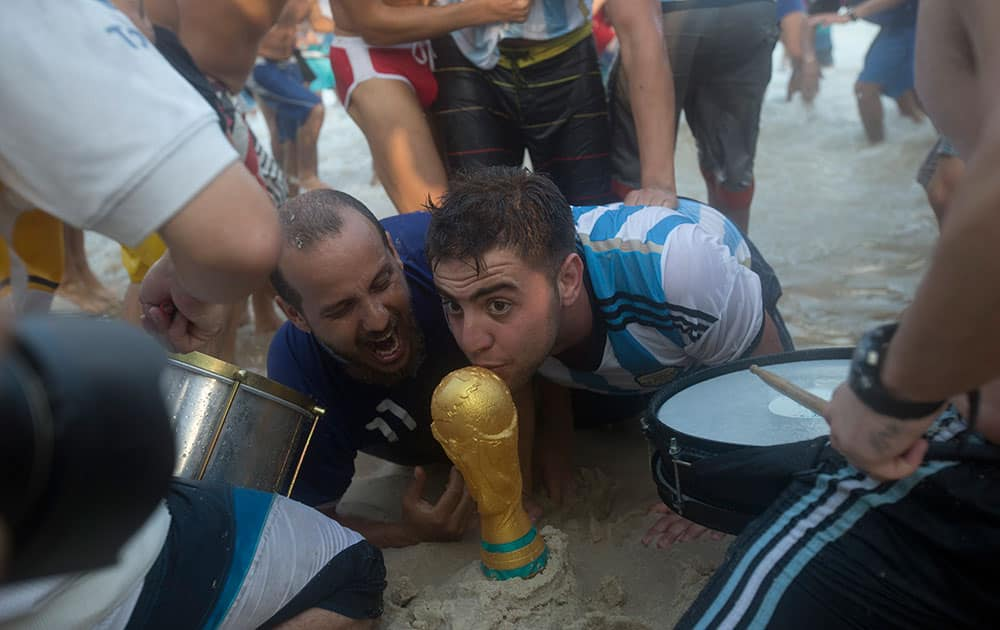 Argentina soccer fans kiss a replica of the World Cup trophy after their team's victory at a World Cup match with Switzerland on Copacabana beach in Rio de Janeiro, Brazil.