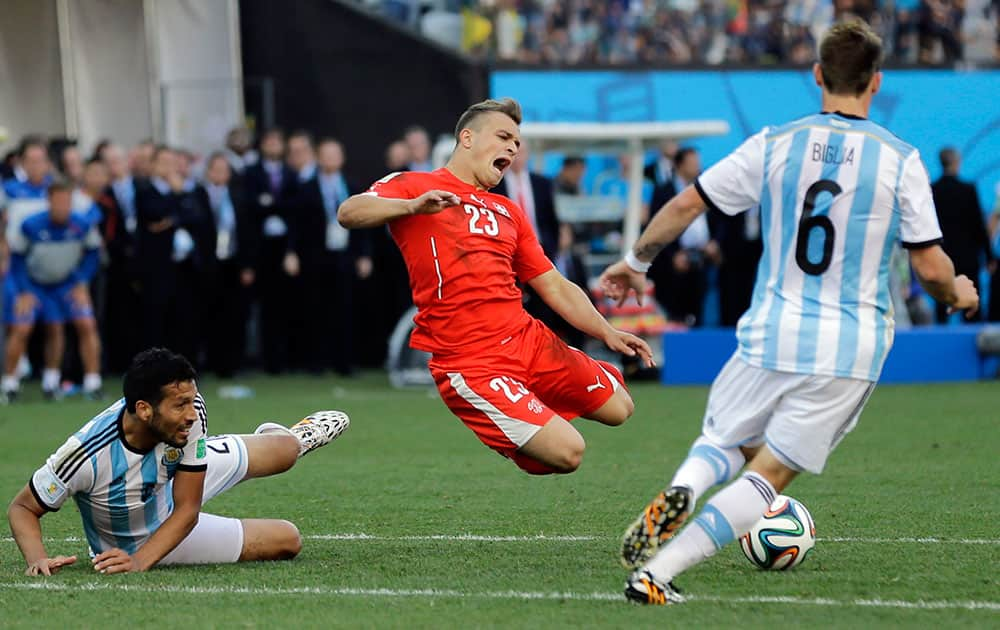 Switzerland's Xherdan Shaqiri is fouled during the World Cup round of 16 soccer match between Argentina and Switzerland at the Itaquerao Stadium in Sao Paulo, Brazil.