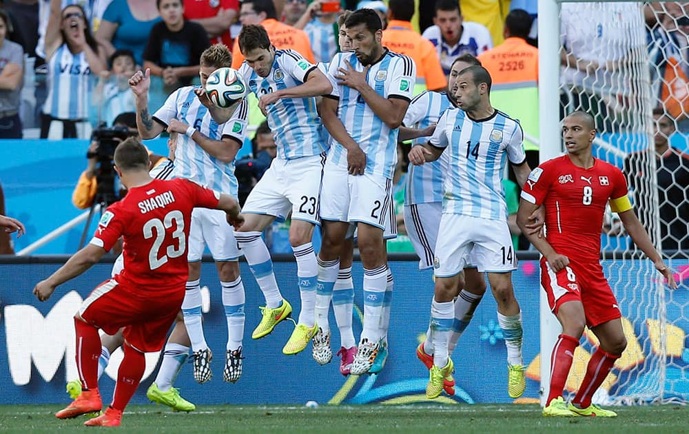Argentina's defensive wall blocks a free kick by Switzerland's Xherdan Shaqiri, left, on the last minutes of their World Cup round of 16 soccer match at the Itaquerao Stadium in Sao Paulo, Brazil.