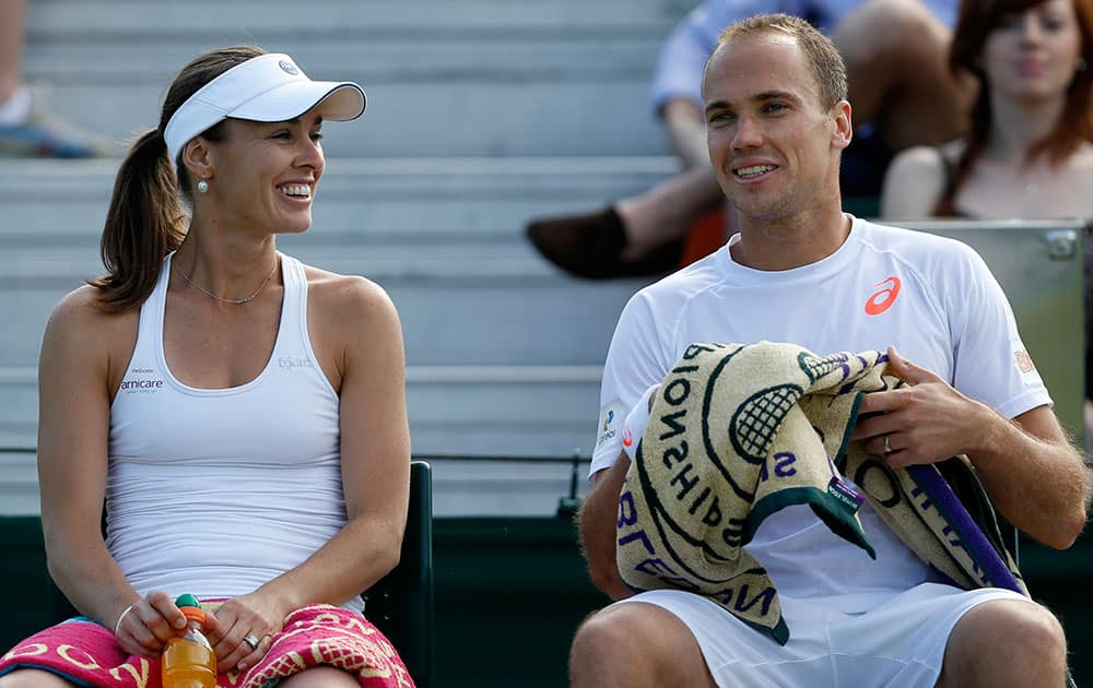Martina Hingis of Switzerland, left, talks to playing partner Bruno Soares of Brazil during a game break in their mixed doubles match against Nicholas Monroe of the US and Shuai Zhang of China at the All England Lawn Tennis Championships in Wimbledon.