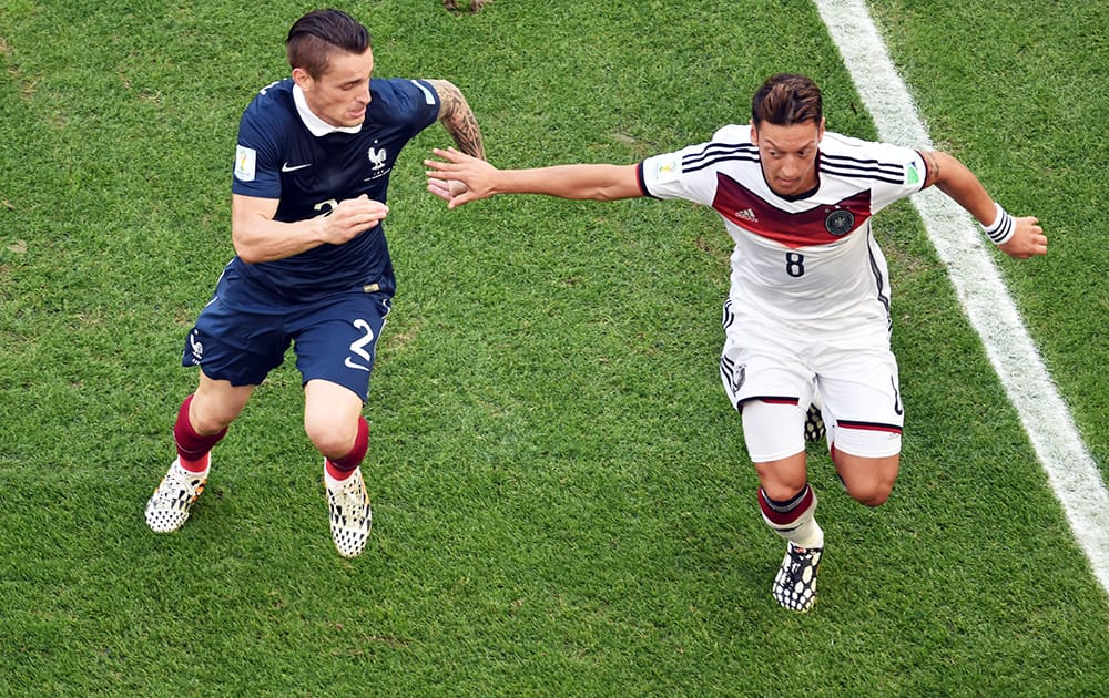 Germany's Mesut Ozil, right, holds off France's Mathieu Debuchy during the World Cup quarterfinal soccer match at the Maracana Stadium in Rio de Janeiro, Brazil.
