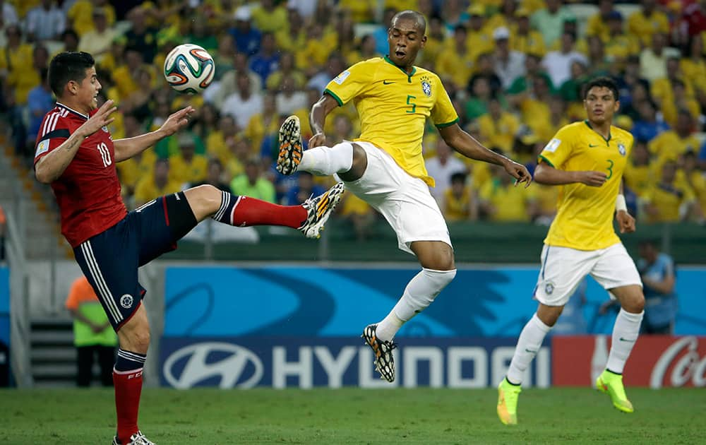 Colombia's James Rodriguez, left, and Brazil's Fernandinho challenge for the ball during the World Cup quarterfinal soccer match between Brazil and Colombia at the Arena Castelao in Fortaleza, Brazil