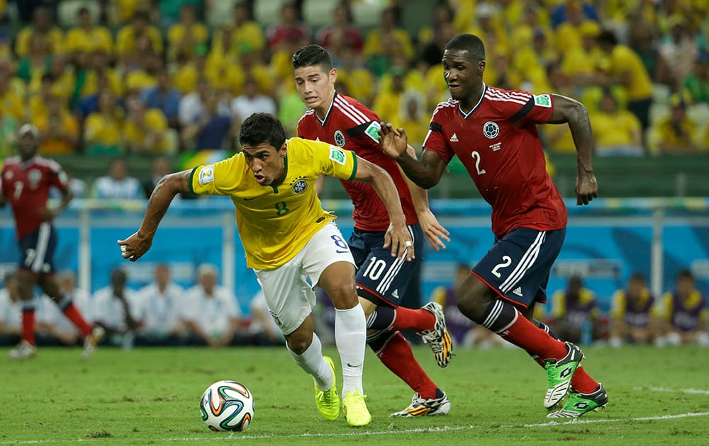 Brazil's Paulinho controls the ball past Colombia's James Rodriguez and Cristian Zapata during the World Cup quarterfinal soccer match between Brazil and Colombia at the Arena Castelao in Fortaleza, Brazil.