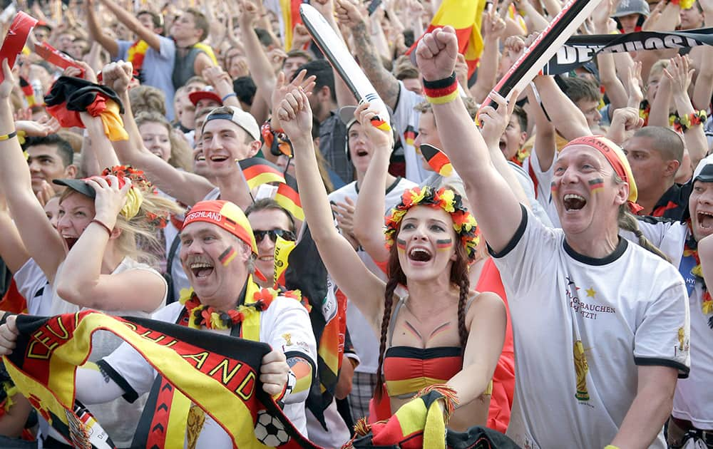 German soccer fans celebrate as they watch the Brazil World Cup quarter final soccer match between Germany and France at a public viewing event in Berlin.