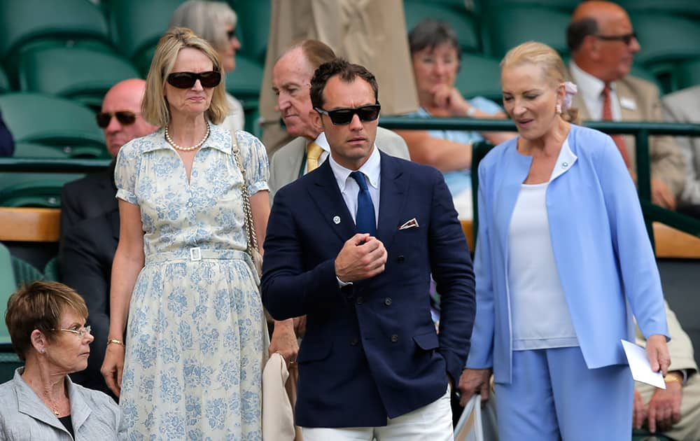 British actor Jude Law, center, walks back into the Royal Box to watch Roger Federer of Switzerland play against Milos Raonic of Canada in their men's singles semifinal match at the All England Lawn Tennis Championships in Wimbledon.