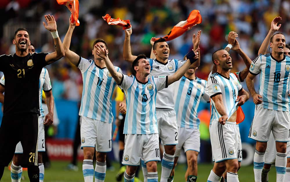 Argentina's Lionel Messi and teammates celebrate at the end of the World Cup quarterfinal soccer match between Argentina and Belgium at the Estadio Nacional in Brasilia, Brazil.